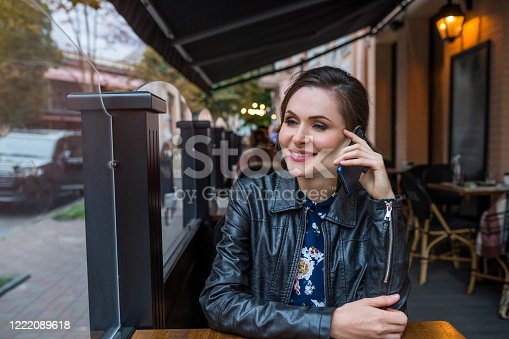 A portrait of a young woman speaking over a cell phone in the cafe.