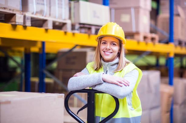 portret van een jonge vrouw magazijnmedewerker. - warehouse worker stockfoto's en -beelden