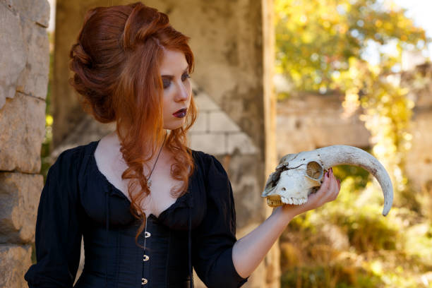 Portrait of a young woman with a make-up and hairstyle on her head, with red hair in black clothes, on the street near the ruins of a building holding a skull with horns stock photo