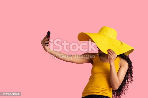 Portrait of a young woman with black hair and big yellow summer hat taking selfie with her smart phone