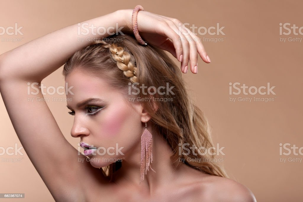 Portrait of a young woman with creative make-up on a beige background royalty-free stock photo
