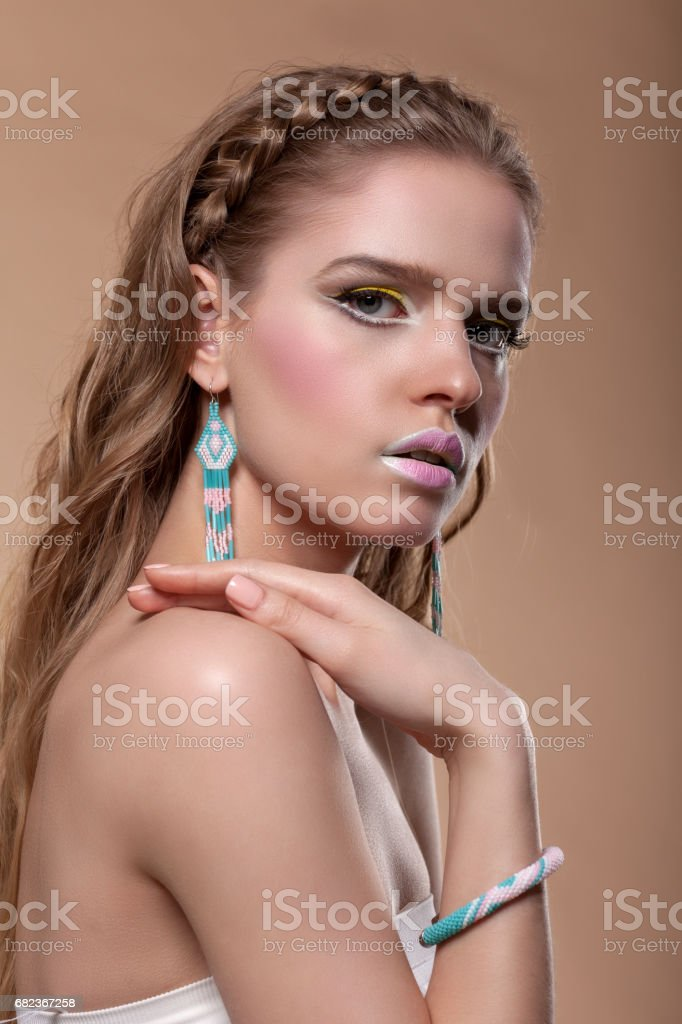 Portrait of a young woman with creative make-up on a beige background royaltyfri bildbanksbilder