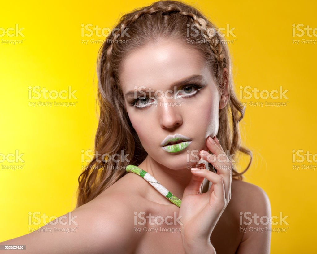 Portrait of a young woman with creative make-up on a yellow background. royalty-free stock photo