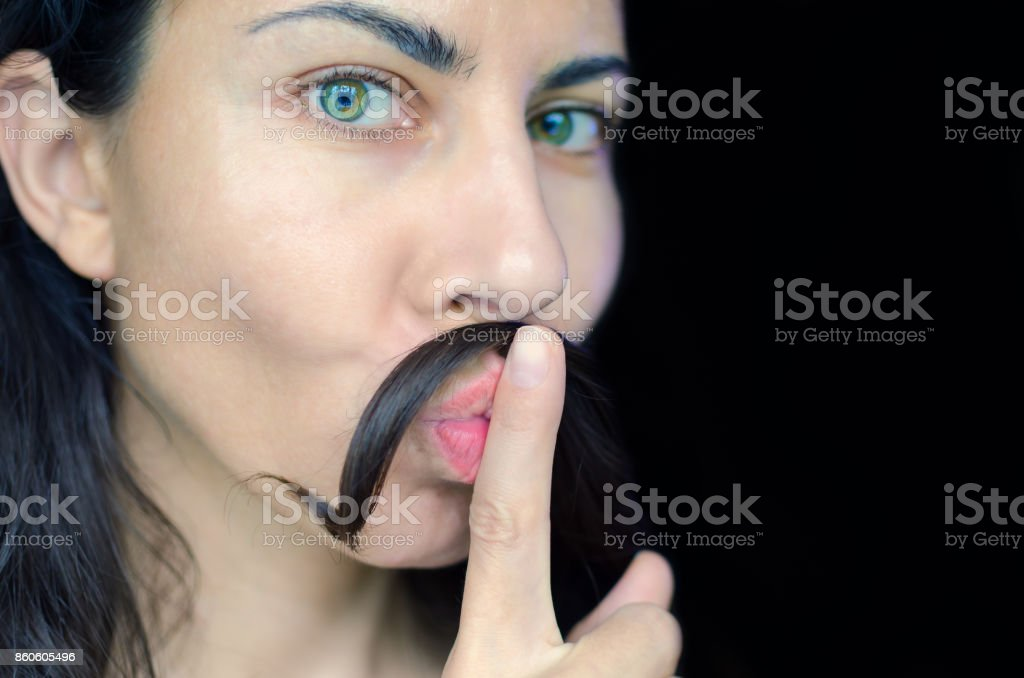 Portrait of a young woman with dark hair has put a strand of her hair on her upper lip. The concept of removing excess hair from women. stock photo
