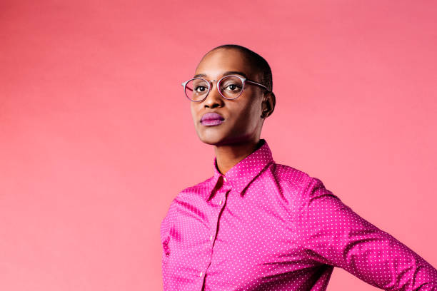 portrait of a young woman with glasses and pink shirt, isolated on pink studio background - carlos david stock pictures, royalty-free photos & images