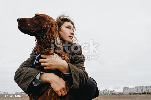 Portrait of a young woman with her dog. Irish setter dog in the arms of the loving mistress.