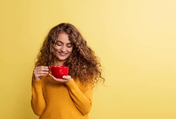 portrait d'une jeune femme avec la cuvette rouge dans un studio sur un fond jaune. - café boisson photos et images de collection