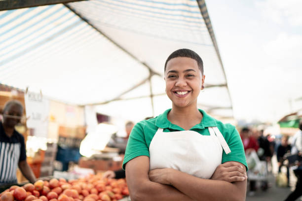 Portrait of a young woman working in a street market Portrait of a young woman working in a street market market vendor stock pictures, royalty-free photos & images