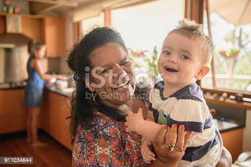 Young boy and mature woman smiling towards camera, mother in background doing dishes