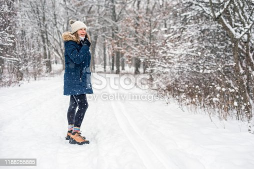 happy woman walking on forest trail in winter with light snow falling