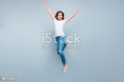 istock Portrait of active positive girl jumping with hands up raised leg isolated on grey background looking at camera enjoying summer time 967121942