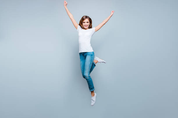 Retrato de ativo positivo menina pulando com as mãos levantadas perna isolados no fundo cinza, olhando para a câmera, aproveitando o horário de verão - foto de acervo