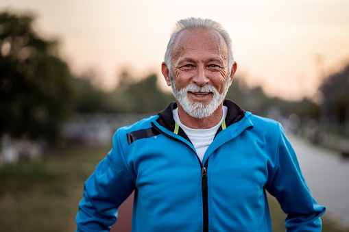 Active senior man is looking at camera and smiling on the running track outdoors.