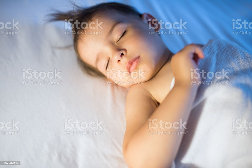 3741d8076 Portrait of adorable baby girl sleeping in white bed at night. Little  toddler taking a nap in dark room in lamplight. Bed time for kids.
