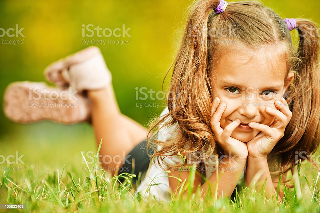 portrait of adorable little girl lying on grass royalty-free stock photo