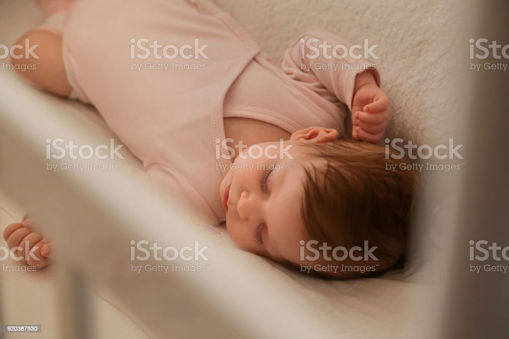 Portrait of adorable newborn baby girl sleeping in a crib stock photo