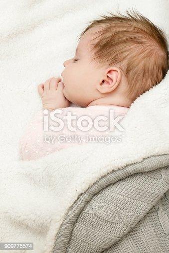istock Portrait of adorable newborn baby girl sleeping 909775574