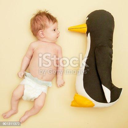 istock Portrait of adorable newborn baby with her penguin friend 901311372