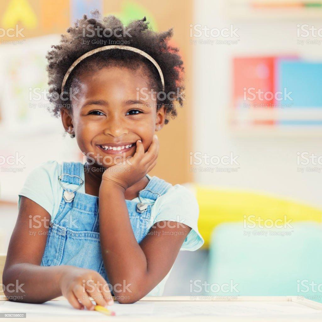 Portrait of adorable preschooler in her classroom stock photo