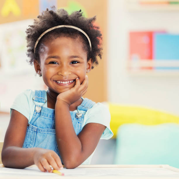 Portrait of adorable preschooler in her classroom Beautiful preschool girl smiles while at school. She is smiling cheerfully at the camera. children only stock pictures, royalty-free photos & images