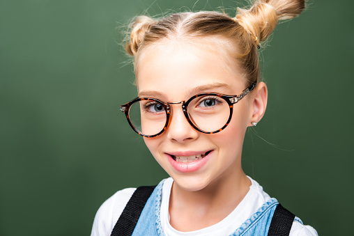 1016623732 istock photo portrait of adorable schoolchild in glasses looking at camera near blackboard 1016623642