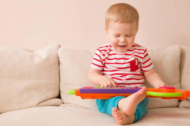 porträt von liebenswert kleinkind jungen auf dem sofa sitzen und spielen spielzeug-klavier. frühes lernen zu hause. kleine musiker. kinder und spielzeug. bildung. im innenbereich. - lautbildungsspiele stock-fotos und bilder