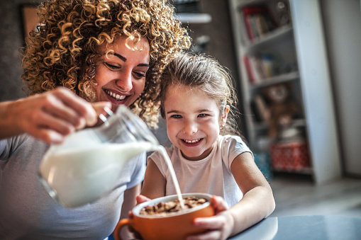 Portrait of adorable young girl and mother having breakfast