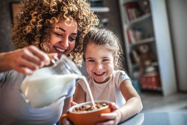 portrait of adorable young girl and mother having breakfast - muesli imagens e fotografias de stock