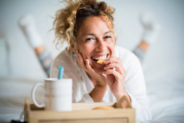 Portrait of adult beautiful woman eating cookie in morning breakfast in the bedroom - home or hotel wake up day with pretty female people lay down with biscuit and tea stock photo