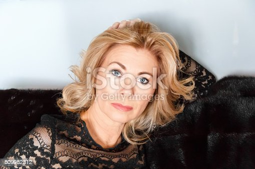 Horizontal portrait of adult blond woman with makeup on black fur