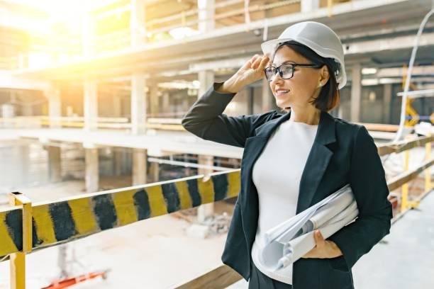 retrato de constructor femenino adulto, ingeniero, arquitecto, inspector, gerente en obra. mujer con plan, mirando a la construcción - arquitecta fotografías e imágenes de stock