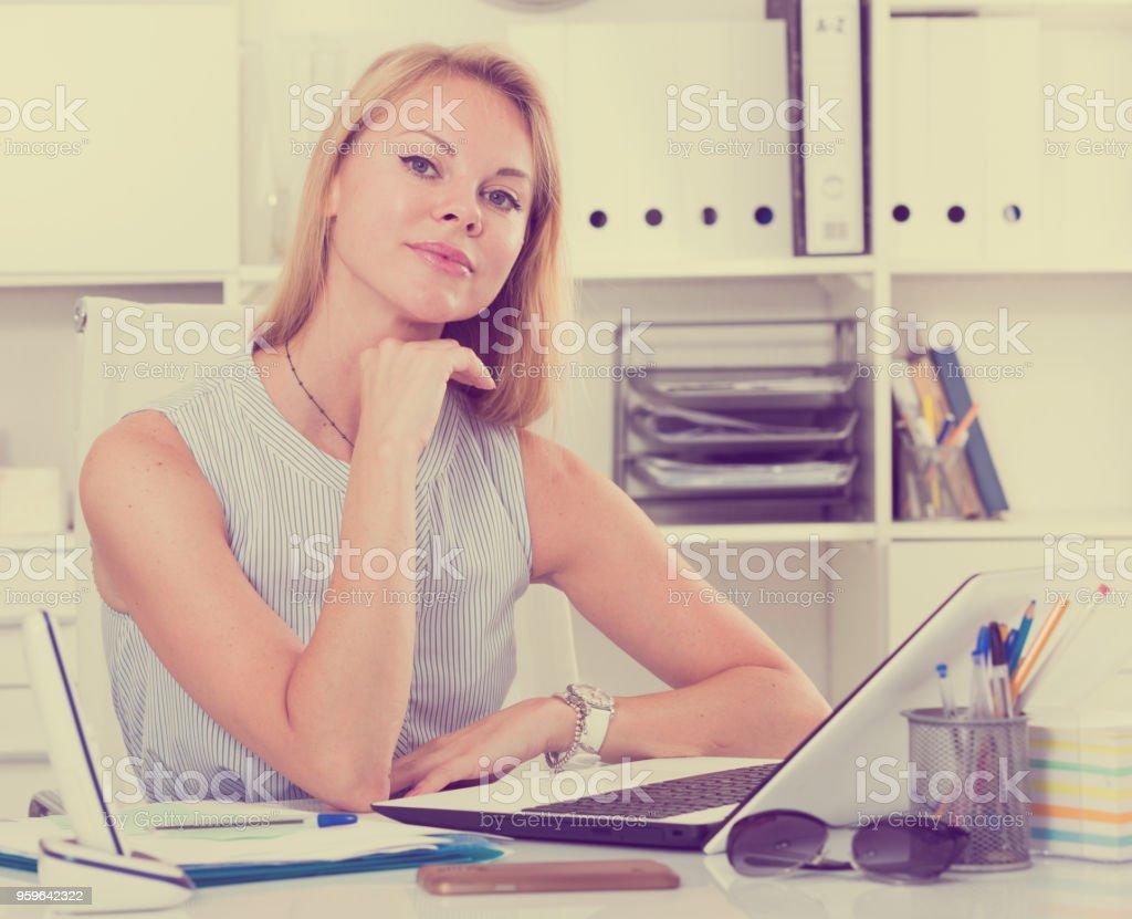 Retrato de muchacha adultos sentados en el lugar de trabajo y sonriendo en la oficina - Foto de stock de 20 a 29 años libre de derechos