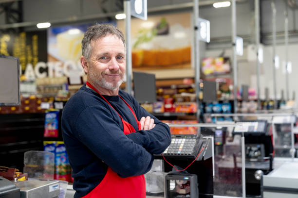 Portrait of adult male cashier at the supermarket facing camera smiling with arms crossed Portrait of adult male cashier at the supermarket facing camera smiling with arms crossed - Focus on foreground sales clerk stock pictures, royalty-free photos & images