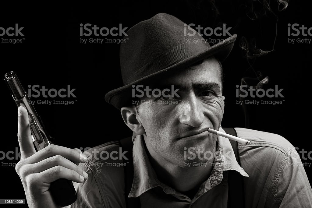 Portrait of adult man holding gun and smoking royalty-free stock photo