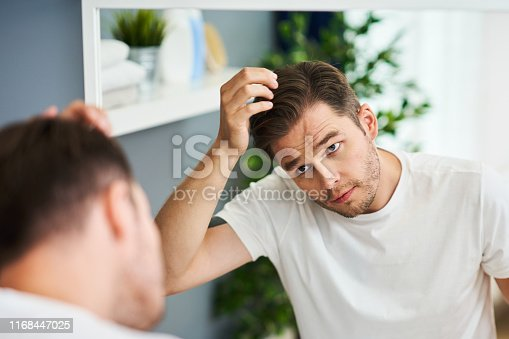 Adult man checking hair condition the bathroom