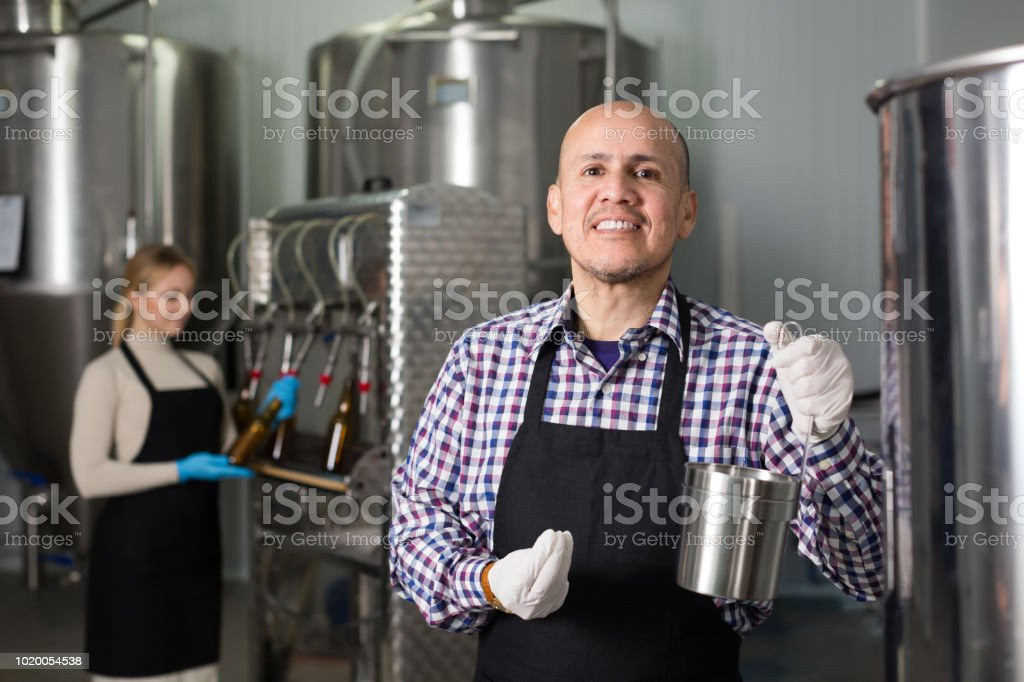 Portrait of adult positive male brewery worker stock photo