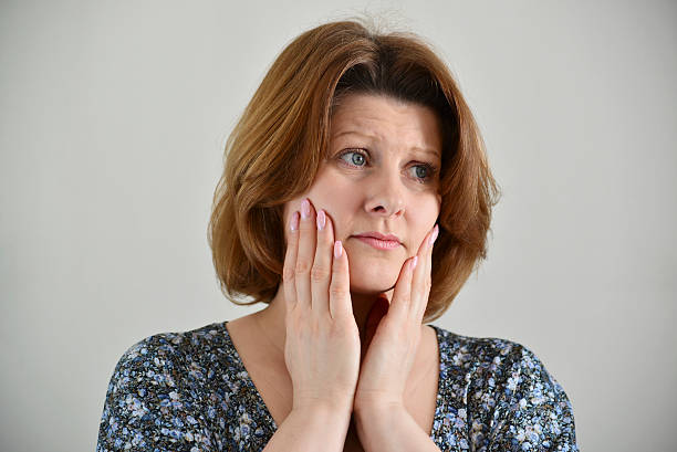 portrait of adult sad female on light background - deplorable stock pictures, royalty-free photos & images