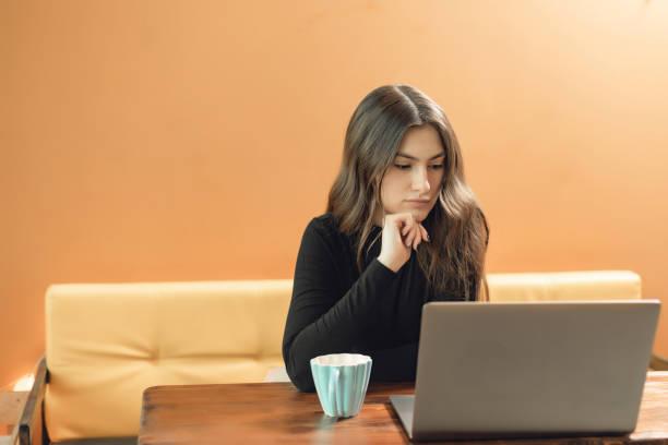Porträt der erwachsenen Frau auf gelbem Hintergrund. Konzept mit Kopierraum. Sie arbeitet mit grauem modernen Laptop und trinkt ein heißes Getränk, zum Beispiel Kaffee oder Tee – Foto
