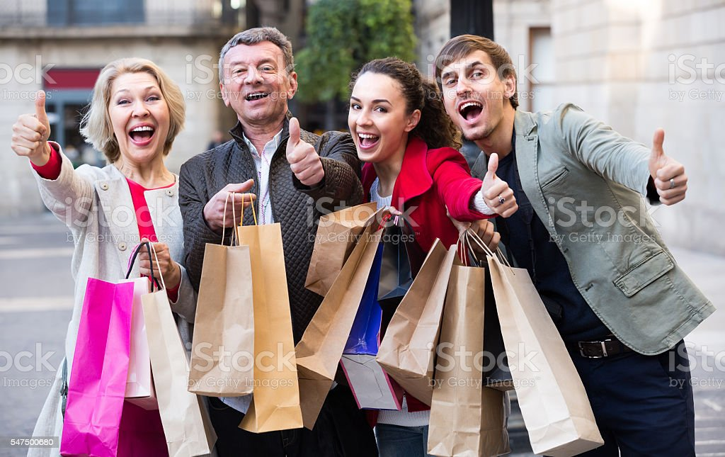 Portrait of adults with packages outdoors stock photo