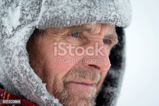 Portrait of a senior man with beard in the mountains, snowing, windy, Alps, Europe.