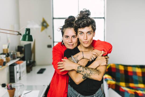 portret van aanhankelijk homoseksueel koppel thuis - lesbische stockfoto's en -beelden