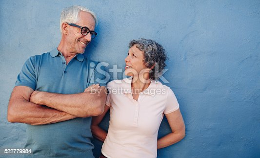 529076288 istock photo Portrait of affectionate mature couple against a blue wall 522779984