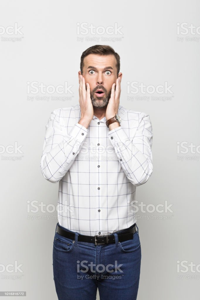 Portrait of afraid businessman, grey background Portrait of worried businessman wearing white shirt and jeans, standing with hand on cheeks against grey background. Studio shot. 30-39 Years Stock Photo