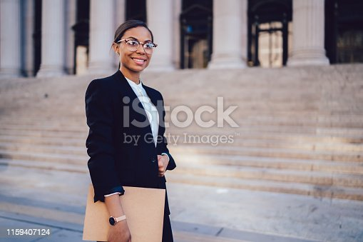 Portrait of African American businesswoman with successful career dressed in formal wear standing against architecture office building with folder in hands. Experienced woman entrepreneur smiling