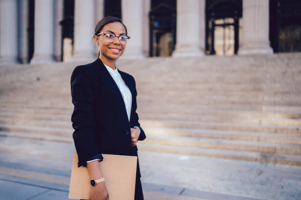Portrait of African American businesswoman with successful career dressed in formal wear standing against architecture office building with folder in hands. Experienced woman entrepreneur smiling stock photo