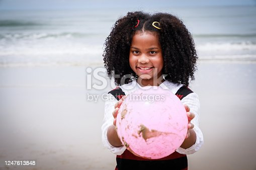 Portrait of African American girl smiling and holding a pink ball on the beach. Happy vacation holiday. Relaxation in vacation in the summer concept.