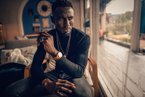 portrait of african american man holding cigar on hand in coffee shop.