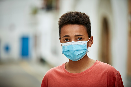 Portrait of african american teenager wearing face mask for COVID-19