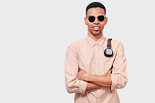 istock Portrait of African American young man with headphones on shoulders, looking to the camera. Afro male student wearing sunglasses, casual shirt, posing on white studio wall 1172152071