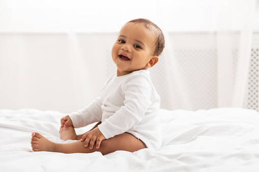Portrait Of Adorable African American Baby Toddler Sitting On Bed And Smiling Looking At Camera Posing In Bedroom At Home. Happy Childhood And Child Care Concept
